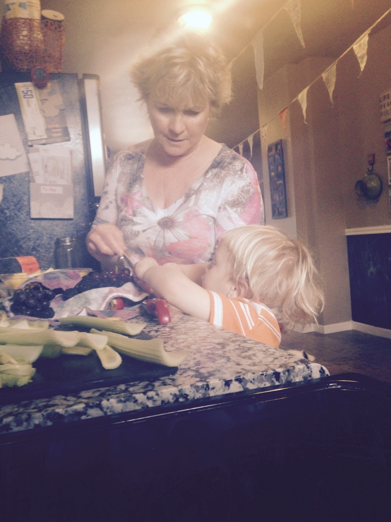 Leif helping Grandma Christine make fruit kabobs for his party